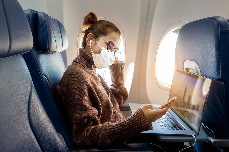 Young woman wears face mask traveling by air during times of coronavirus
